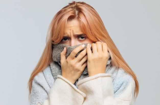 Больная женщина, завернутая в шарф, смотрит в камеру, closeup.flu сезона