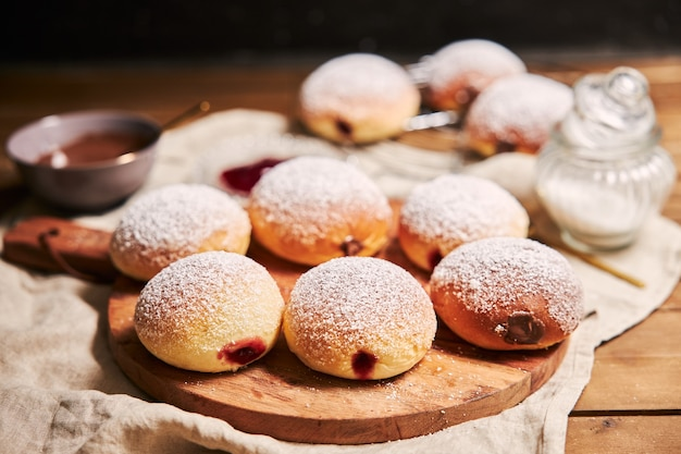 Closeup of fluffy doughnuts filled with jam on a tray on the table under the lights