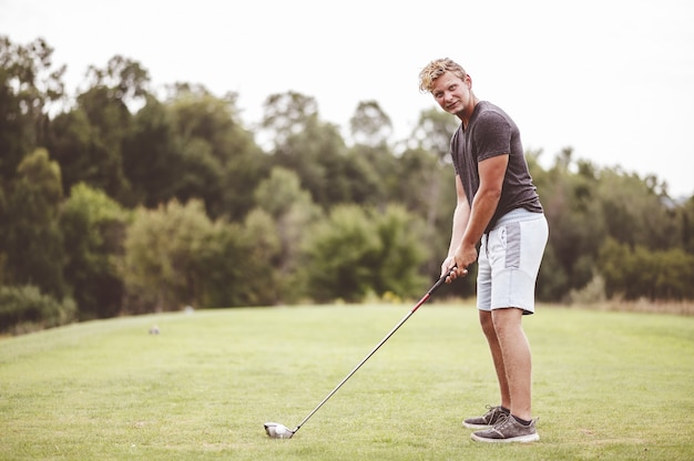 Closeup focus portrait of a young man playing golf