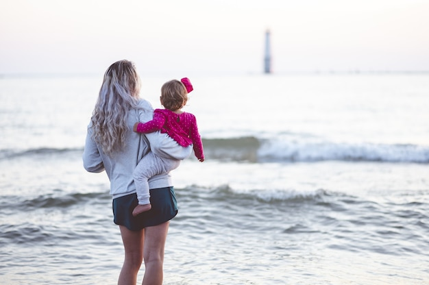 Closeup focus shot from behind of a mother and her child looking at the sea