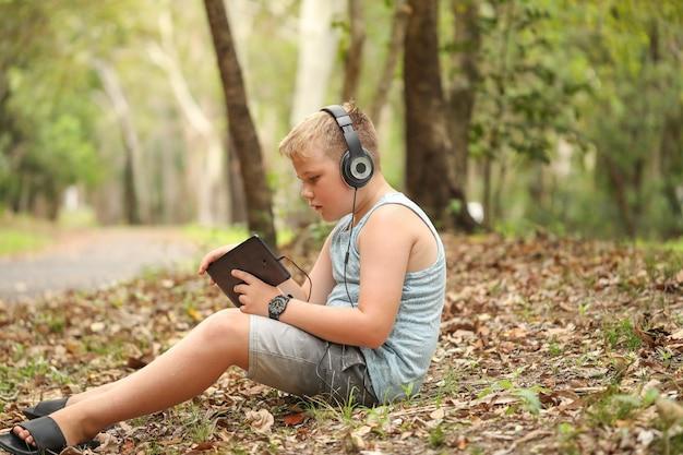 Primo piano di un bambino che usa un tablet e indossa le cuffie in natura