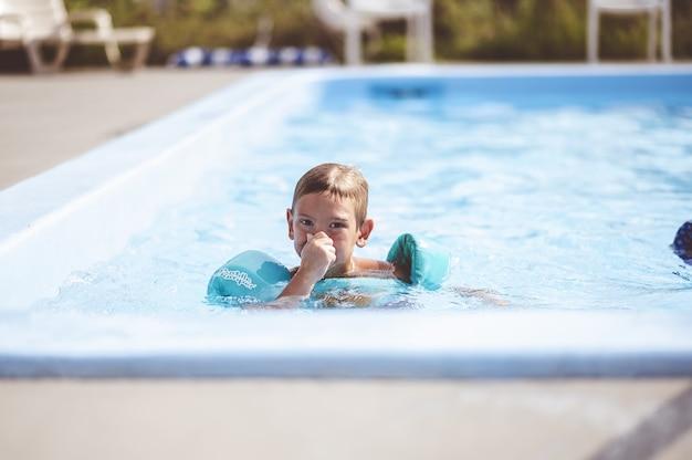 수영장에서 수영하는 귀여운 어린 소년의 근접 촬영 초점 샷