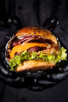 Снимок крупным планом руки с черными перчатками, держащей вкусный гамбургер