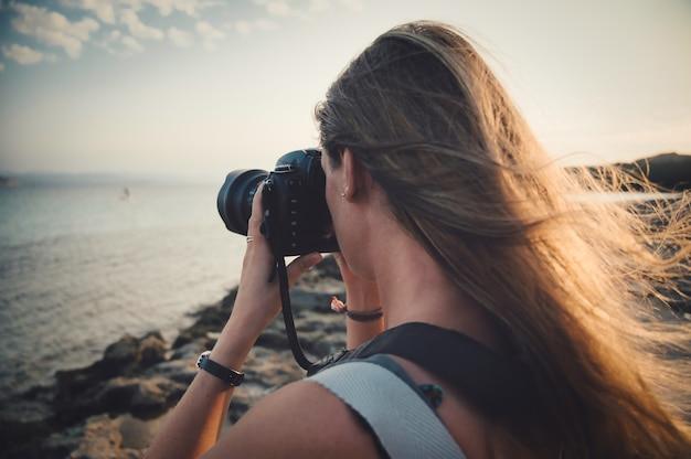 海の写真を撮る女性のクローズアップフォーカスショット-写真撮影の概念