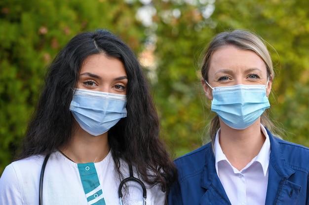 야외에서 얼굴 마스크를 착용하는 젊은 의사의 근접 촬영 초점 샷