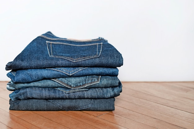 Closeup of folded jeans on top of each other on the floor under the lights