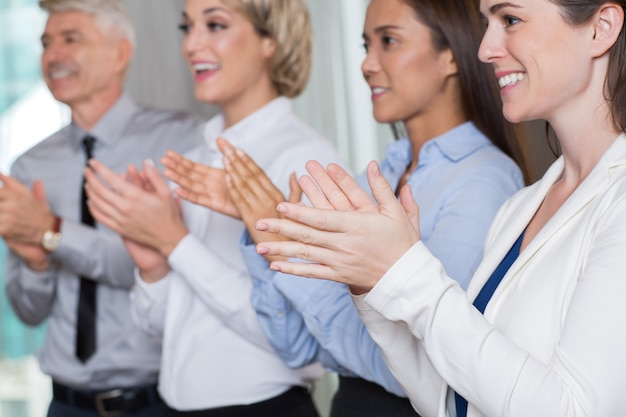 Closeup of four smiling business people applauding
