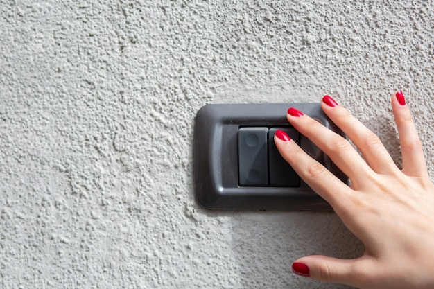 Closeup fragment of woman hand pressing the button of a doorbell on concrete wall. space for text