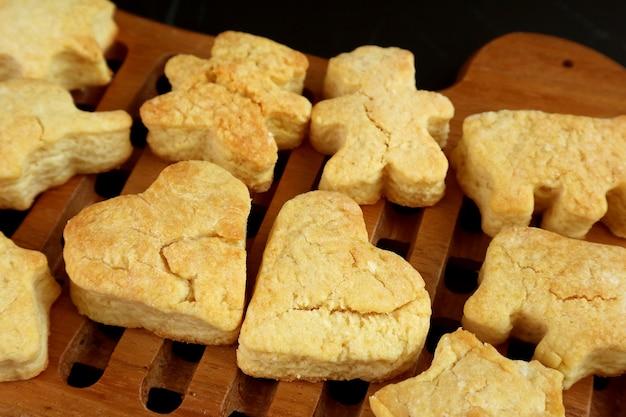 Closeup of fresh baked homemade heart shaped butter cookies on wooden breadboard