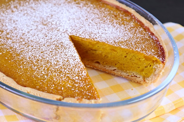 Closeup fresh baked and partly cut homemade pumpkin pie sprinkled with icing sugar