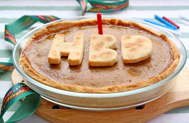 Свежий запеченный тыквенный пирог крупным планом со свечой, готовый к празднованию дня рождения