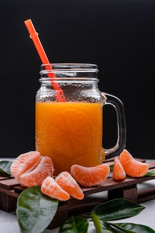 Closeup of fresh mandarin juice in a glass jar with a plastic reusable straw on a wooden tray