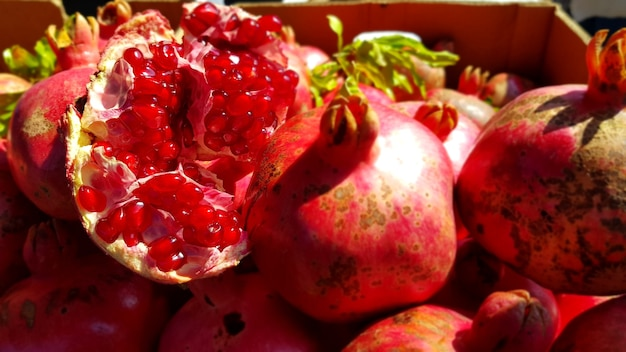 Closeup of fresh pomegranates in a box under the sunlight in the bazaar