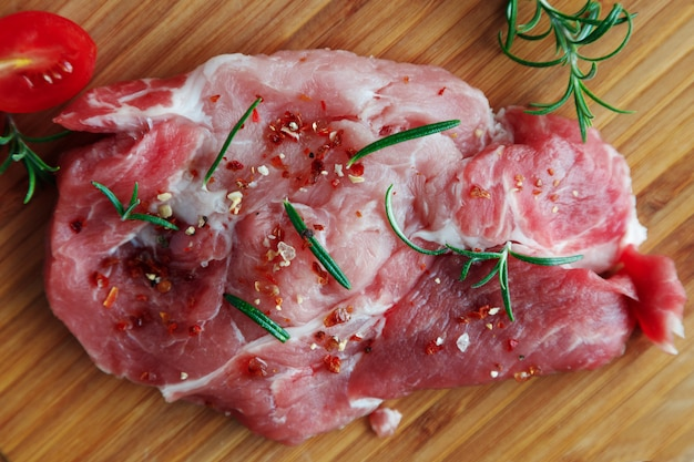 Closeup on fresh pork steak in spices and rosemary leaves on a wooden board.