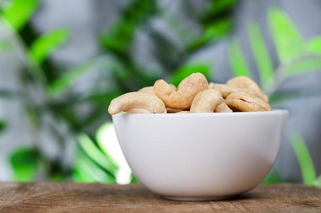 キッチンテーブルの新鮮な生のカシューナッツ、健康的で高カロリーの生のカシューナッツ、美しい曲がったカシューナッツのクローズアップ