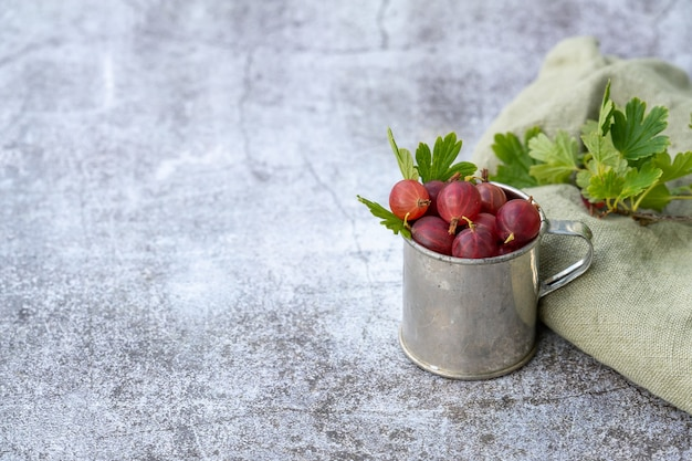 Closeup of fresh red gooseberries in a small bucket, placed on a grunge surface