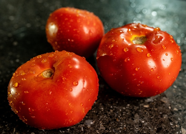 Closeup of fresh ripe tomatoes with water droplets on a black granite kitchen counter surface