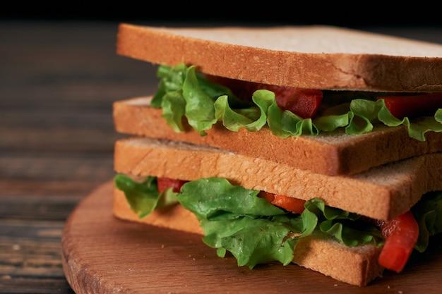 Сэндвич со свежими помидорами крупным планом на деревянном столе