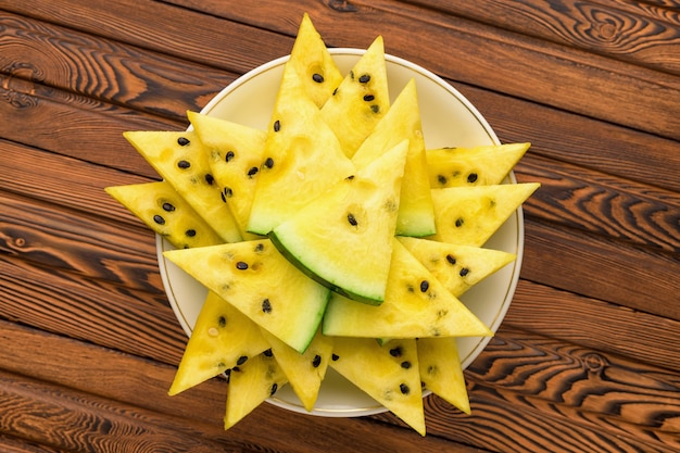 Closeup of fresh yellow watermelon slices on white plate