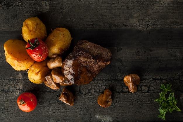 木製の古いボード上のジャガイモとジャガイモと揚げ肉のクローズアップジャガイモとキノコと揚げ肉
