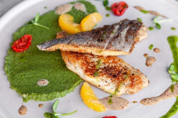 Closeup fried sea bass fillet with green pea puree, tomatoes, sauce, orange slices.