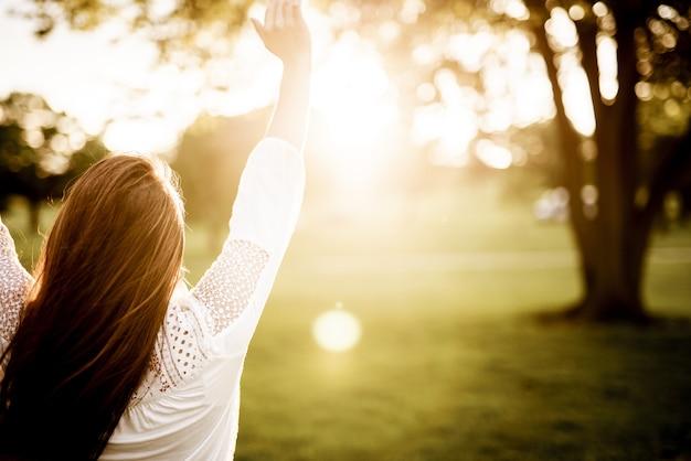 흐린 배경으로 하늘을 향해 그녀의 손을 잡고 여성 뒤에서 근접 촬영