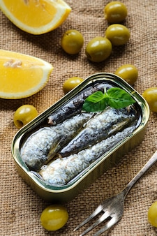 Closeup from above of a can of sardines in oil, with some basil leaves, lemon wedges and olives on sackcloth