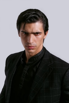 Портрет крупного плана переднего уверенно красивого молодого человека в черной одежде на белой предпосылке. вертикальный вид.
