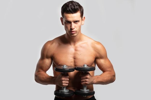 裸の胴体、ダンベルでトレーニング、フィット感、強いハンサムな若い男のクローズアップの正面の肖像画