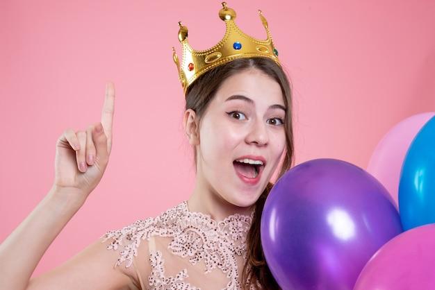 クローズアップ正面図指を上に向けて風船を保持している王冠を持つかわいいパーティーの女の子