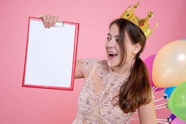 クリップボードを保持している王冠とクローズアップ正面図かわいいパーティーの女の子