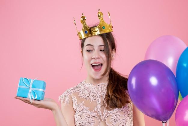 クローズアップ正面図現在と風船を保持している王冠を持つかわいいパーティーガール