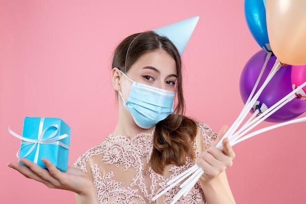 Primo piano vista frontale ragazza carina festa con corona e maschera che tiene palloncini e regalo