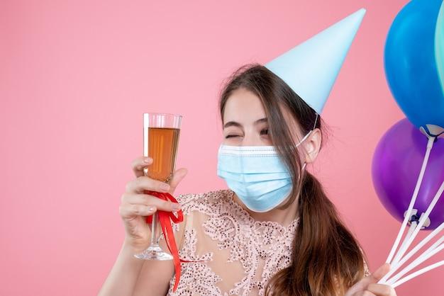 Primo piano vista frontale ragazza carina festa con corona e maschera che tiene palloncini tostatura