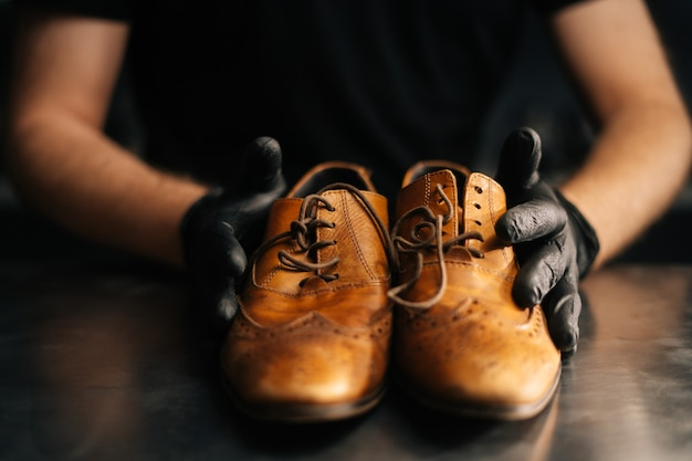 Closeup front view of hands of shoemaker shoemaker in black gloves holding old worn light brown leat...