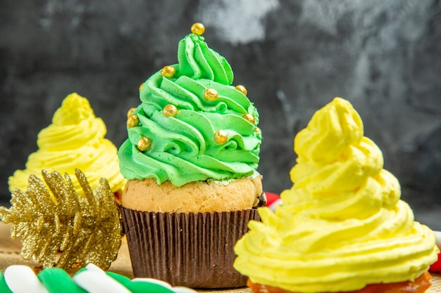 Closeup front view mini cupcakes xmas ornaments xmas candies on newspaper on dark background