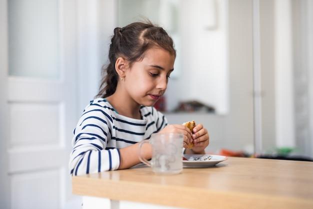 Крупным планом вид спереди девушки начальной школы, едящей гамбургер дома