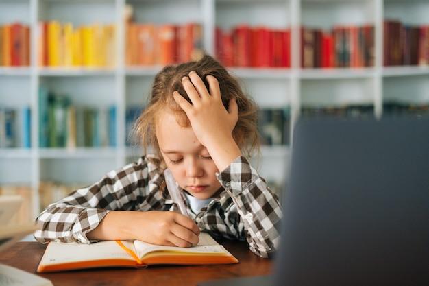 Крупным планом вид спереди измученной милой школьницы начальной школы, делающей домашнее задание, держа ручку
