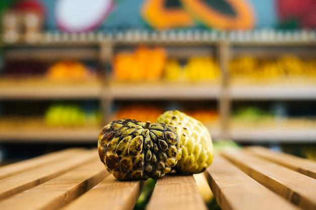 과일과 야채에 있는 나무 팔레트에 누워 있는 신선한 육즙이 많은 아노나 스콰모사의 전면 전망