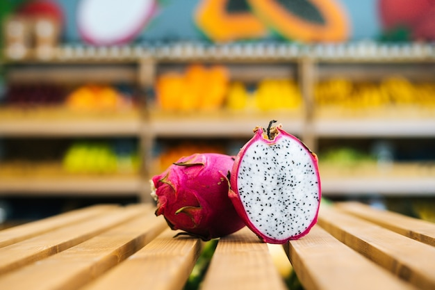 果物と野菜のセクションで木製パレットの上に立っている新鮮なジューシーなピタハヤのクローズアップ正面図