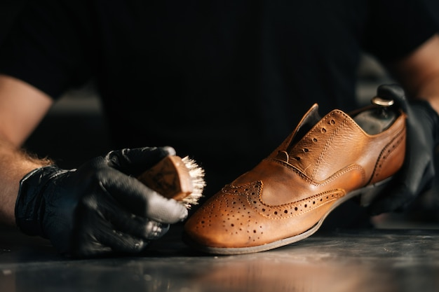 Closeup front view of unrecognizable shoemaker cleaning with brush old light brown leather shoes