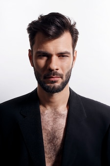 Closeup frontal  bearded man posing in black suit, with naked torso