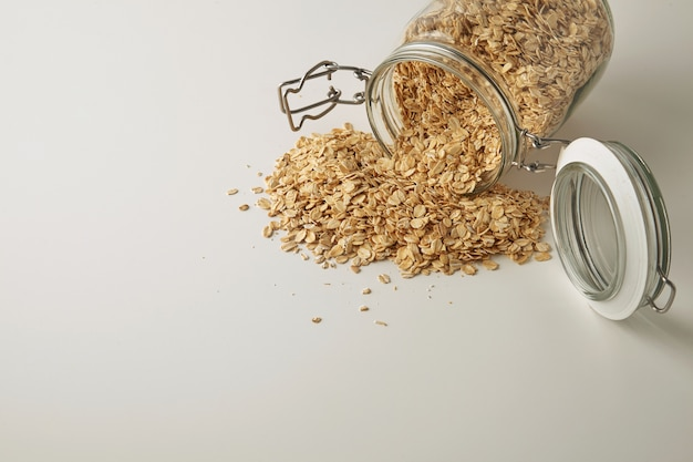 Closeup full opened rustic jar with healthy rolled oats spread out isolated in side on white table side view