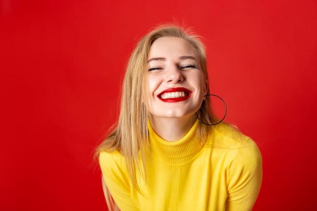 Крупным планом веселое лицо девушки смеется, смотрит в камеру - широкая улыбка