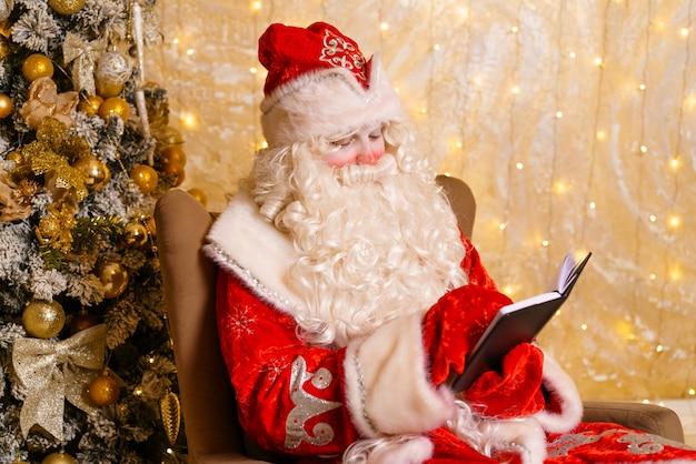 클로 우즈 업 재미 펑키 뚱뚱한 산타 클로스 메모장을 들고 무엇을 결정 하는 위시리스트의 계획에 대해 생각...