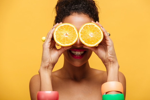 Closeup funny mixed-race woman with fashion accessories having fun and covering eyes with two halves of orange isolated, over yellow wall