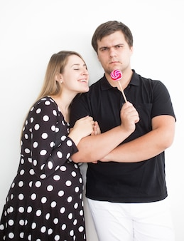 Closeup funny portrait of young man holding lollipop and giving in to girlfriend