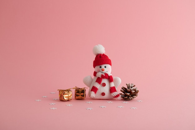 Closeup of a funny snowman, small gift boxes, and a pine cone in the pink background