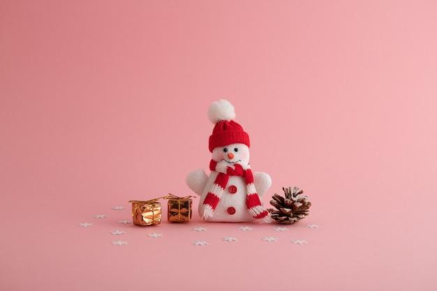 Primo piano di un divertente pupazzo di neve, piccole confezioni regalo e una pigna sullo sfondo rosa