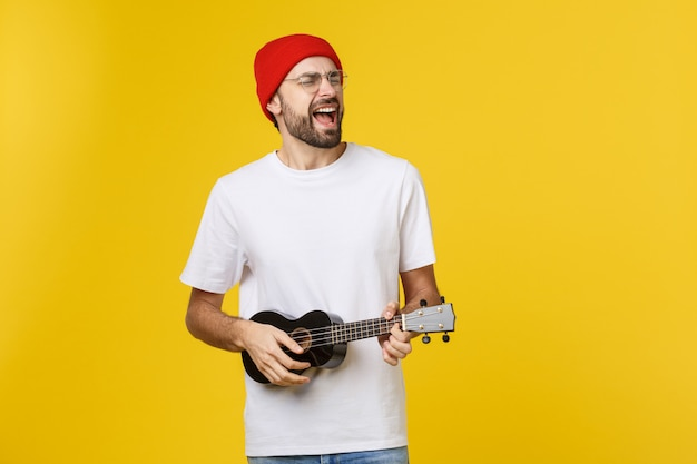 Closeup of funny young man playing a guitar. isolated on yellow gold